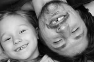 Father and daughter smiling with missing teeth