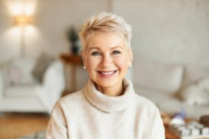 an older woman wearing a sweater and smiling, showing off her new dental implants in Tysons