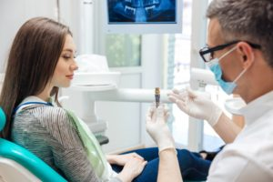 a woman listening as her dentist explains the parts of a dental implant