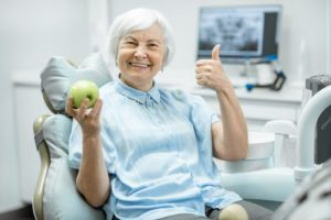 an older woman sitting in the dentist's chair holding an apple and giving a thumbs up while smiling