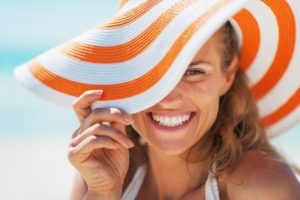 Woman in sun hat smiles after visiting Tysons, VA dentist
